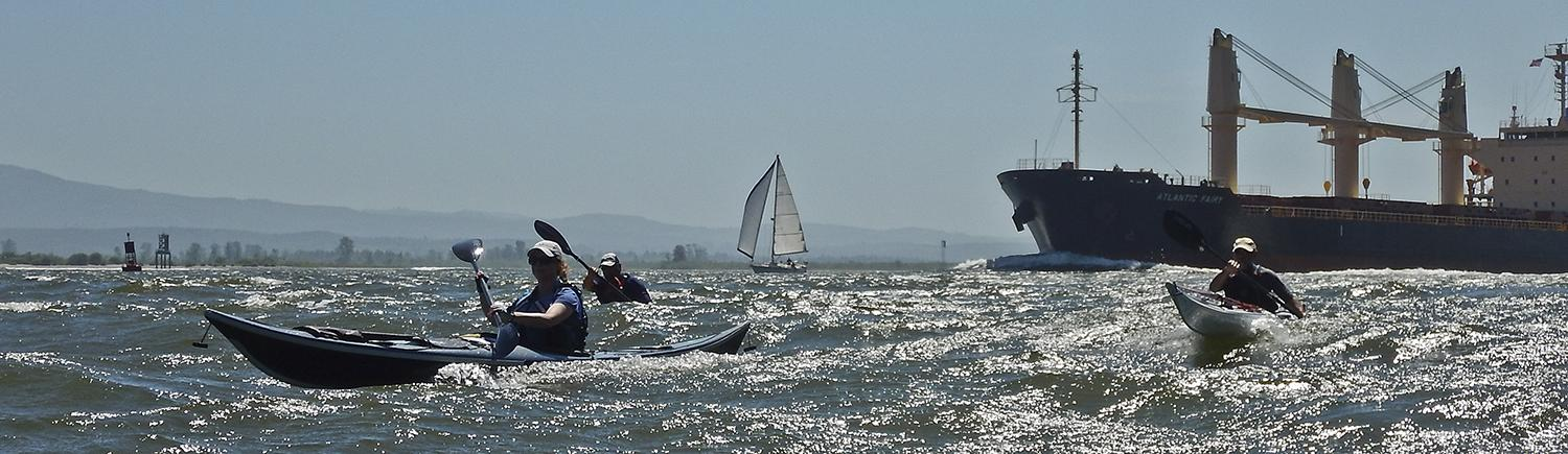 three kayakers paddle through choppy water, with a barge and sailboat in the distance