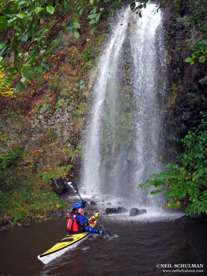 kayaker faces a small waterfall