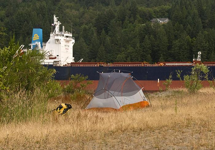 tent on Quill Island with large barge passing in the background